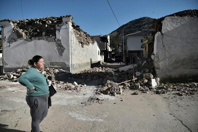 A woman stands by damaged old buildings in the village of Damasi, near the town of Tyrnavos, after a strong 6.3-magnitude earthquake hit the Greek central region of Thessaly on March 3, 2021