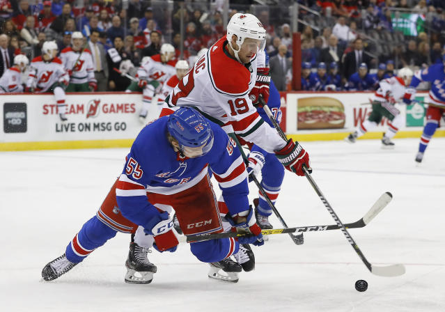 New Jersey Devils center Travis Zajac (19) and New York Rangers defenseman Ryan Lindgren (55) battle for the puck during the second period of an NHL hockey game Saturday, Nov. 30, 2019, in Newark,N.J. (AP Photo/Noah K. Murray)