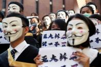FILE PHOTO: University students wearing Guy Fawkes masks pose during a news conference to support anti-government protests before their graduation ceremony at the Hong Kong Polytechnic University in Hong Kong