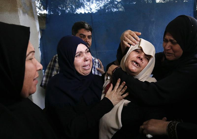 The mother (C) of Palestinian Ahmed al-Taweel, shot dead by Israeli troops during protests along the Gaza-Israel border, mourns at his funeral in central Gaza's Nuseirat camp on October 13, 2018
