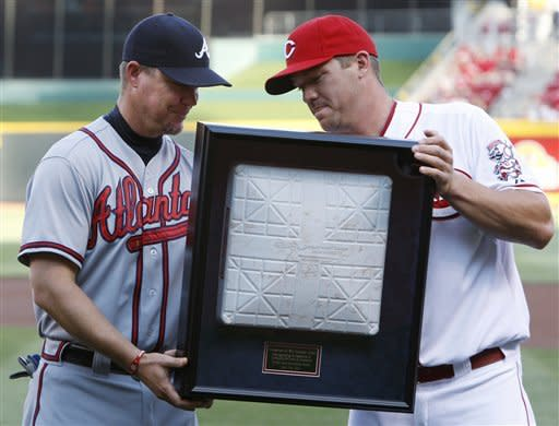 Cincinnati Reds third baseman Scott Rolen, right, presents Atlanta Braves third baseman Chipper Jones with a framed base during ceremonies honoring Jones prior to a baseball game, Thursday, May 24, 2012 in Cincinnati. Jones plans to retire after this season. (AP Photo/Al Behrman)