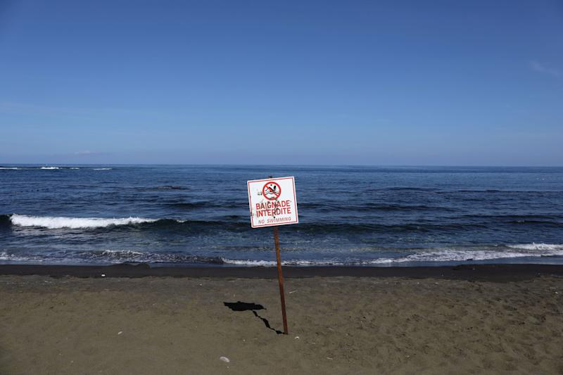 A picture taken on March 1, 2019, shows a sign banning swimming at the L'Étang-Salé beach, on the Indian Ocean island of La Réunion. (Photo: RICHARD BOUHET via Getty Images)