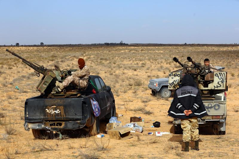 Fighters from the Fajr Libya (Libya Dawn) militia during clashes with forces loyal to Libya's internationally recognised government near the Wetia military air base, some 170 kilometres west of the capital Tripoli on January 5, 2015 (AFP Photo/Mahmud Turkia)