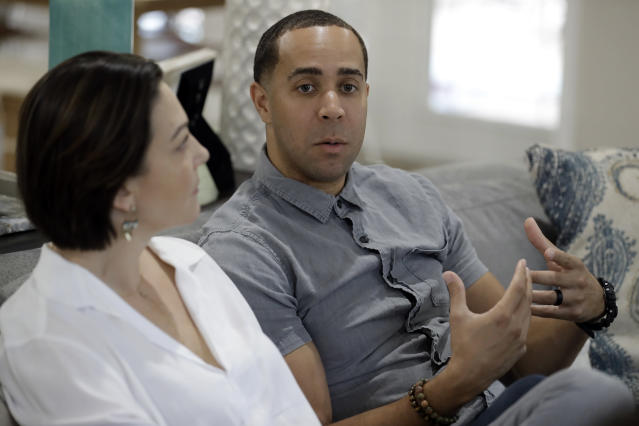 NBA referees Jonathan Sterling, right, gestures as he sits with his wife Lauren Holtkamp-Sterling, the only married couple in NBA refereeing history, during an interview at their home Thursday, Oct. 3, 2019 in Tampa, Fla. (AP Photo/Chris O'Meara)