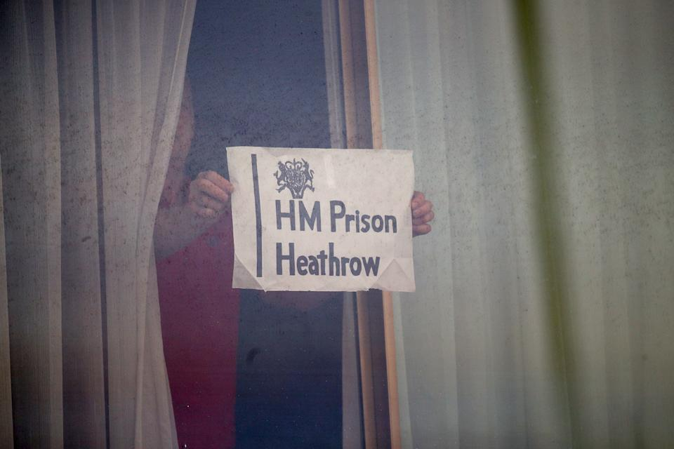 A man holds a sign against a window at the Renaissance London Heathrow Hotel, near Heathrow Airport, London, a Government-designated quarantine hotel being used for travellers to stay during a 10-day quarantine after returning to England from one of 33