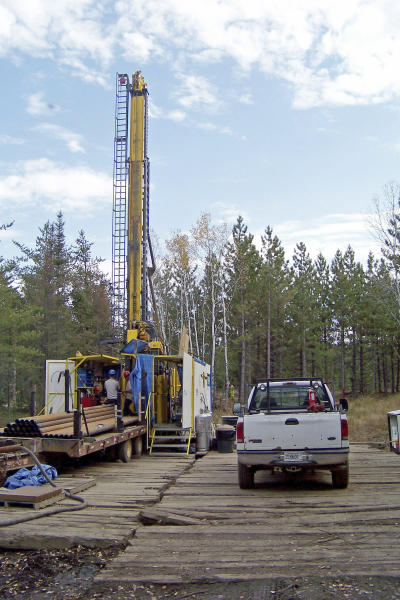 FILE - In this Oct. 4, 2011 file photo, a prospecting drill rig bores into the bedrock near Ely, Minn., in search of copper, nickel and precious metals that Twin Metals Minnesota LLC, hopes to mine near the Boundary Waters Canoe Area Wilderness in northeastern Minnesota. The federal Bureau of Land Management has reinstated mineral rights leases for a proposed Twin Metals copper-nickel mine in northeastern Minnesota. The leases cover land in Superior National Forest 9 miles southeast of Ely that encompasses reserves of copper, nickel and precious metals. Environmental groups are fighting the project, fearing mining would spoil the Boundary Waters Canoe Wilderness. Twin Metals Minnesota plans to submit its underground mine proposal in the coming months. (AP Photo/Steve Karnowski,File)