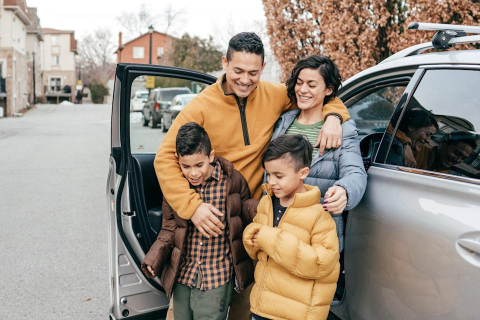 A family of four gather in front a car during colder months
