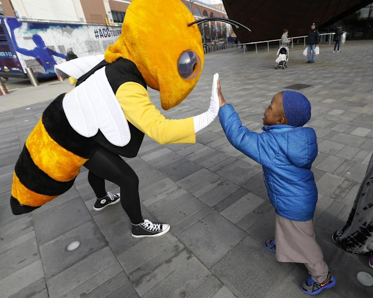 """Four year-old Malik McKenna, right, greets """"Buzz,"""" the Georgia Tech Yellow Jackets' mascot, outside the Barclays Center, Monday, March 6, 2017, in New York. Buzz and 14 other Atlantic Coast Conference mascots took part in a press conference, rode the subway and walked in Main Street Park in downtown Brooklyn to promote the upcoming ACC basketball tournament March 7-11 at the Barclays Center in Brooklyn. (AP Photo/Kathy Willens)"""