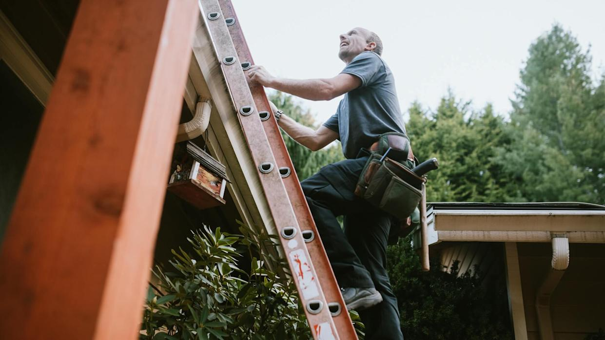 A roofer and crew work on putting in new roofing shingles.