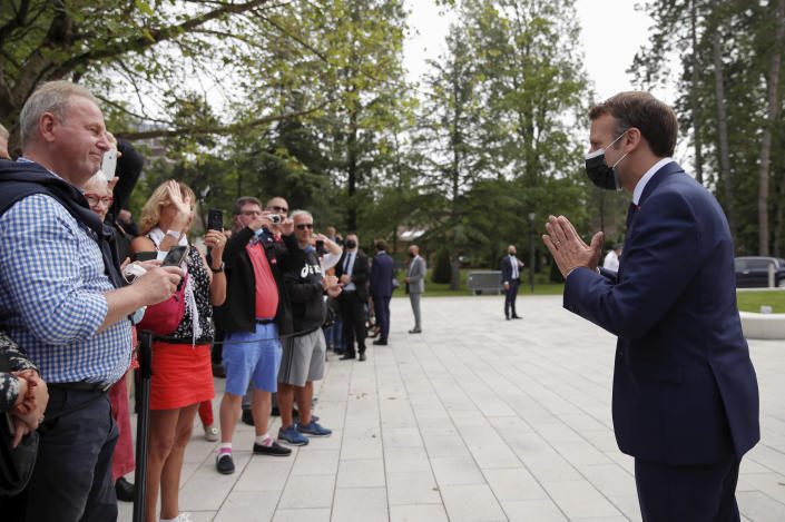 French President Emmanuel Macron greets voters during the first round of French regional and departmental elections, in Le Touquet-Paris-Plage, northern France, Sunday, June 20, 2021. The elections for leadership councils of France's 13 regions, from Brittany to Burgundy to the French Riviera, are primarily about local issues like transportation, schools and infrastructure. But leading politicians are using them as a platform to test ideas and win followers ahead of the April presidential election. (Christian Hartmann/Pool via AP)