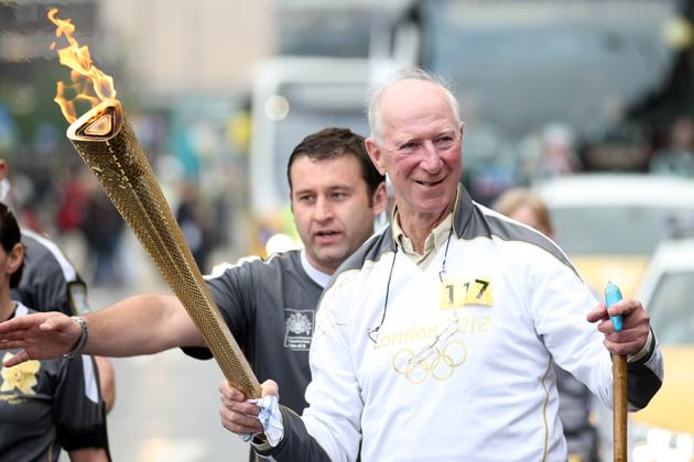 In this handout image provided by LOCOG, Torchbearer 117 Jack Charlton carries the Olympic torch on June 15, 2012 in Newcastle upon Tyne, England. The Olympic Flame is now on day 28 of a 70-day relay involving 8,000 torchbearers covering 8,000 miles.  (Photo by LOCOG via Getty Images)
