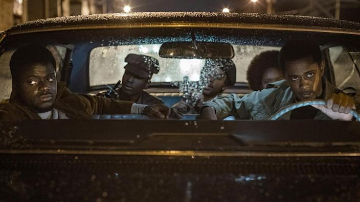"Daniel Kaluuya at left and LaKeith Stanfield behind the wheel of a car in a scene from ""Judas and the Black Messiah."""