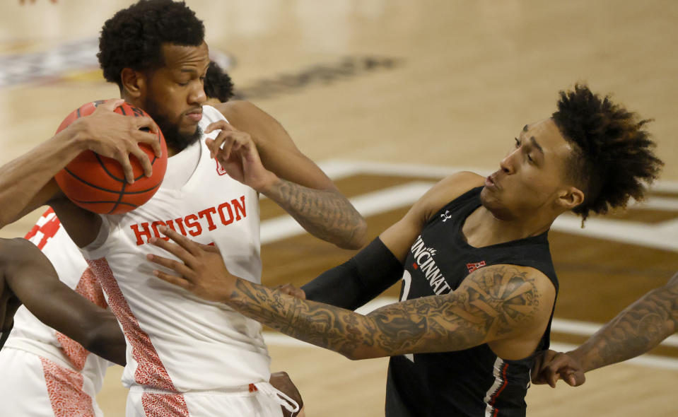 Houston forward Justin Gorham (4) and Cincinnati guard Jeremiah Davenport (24) fight for a rebound during the second half of an NCAA college basketball game in the final round of the American Athletic Conference men's tournament Sunday, March 14, 2021, in Fort Worth, Texas. (AP Photo/Ron Jenkins)