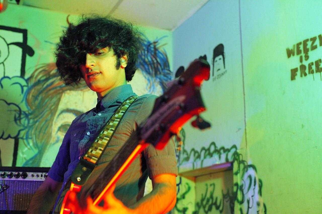 """This 2012 photo shows Yellow Dogs band member, bassist Koroush """"Koory"""" Mirzaei at the Death By Audio performance space in the Brooklyn borough of New York. Police say a musician who shot and killed three other Iranian men inside a New York City apartment before committing suicide was upset because he had been kicked out of an indie rock band. Ali Akbar Mohammadi Rafie gunned down the men just after midnight on Monday, Nov. 11, 2013. Victims Soroush and Arash Farazmand were brothers who played in a band called the Yellow Dogs. The third victim, Ali Eskandarian was also a musician. After the shooting, investigators found a guitar case on a rooftop they believe the shooter may have used to carry the assault rifle used in the attack.(AP Photo/Danny Krug) NO SALES"""