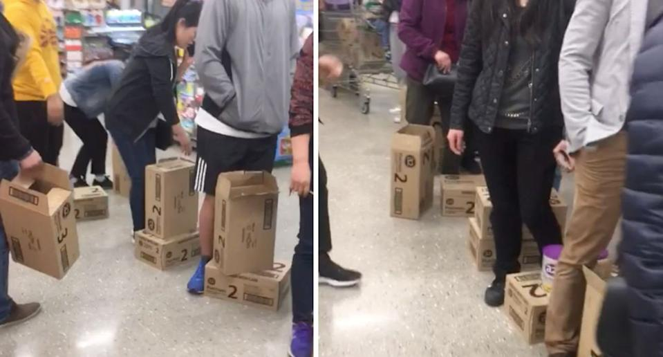 Customers stand with boxes of formula in Woolworths despite their two tin limit. Source: Reddit