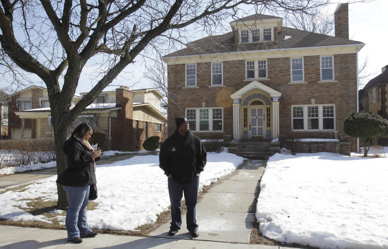 Real estate agent Nancy Williams, left, searches her handheld database as Detroit police officer William Booker-Riggs stands outside a house in the Boston Edison section of Detroit, Wednesday, Feb. 16, 2011. The city hopes its renovated homes incentive will lure police officers to move into and stabilize Detroit neighborhoods.(AP Photo/Carlos Osorio)
