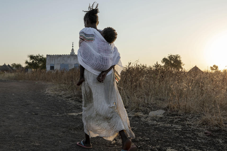 A Tigrayan woman who fled the conflict in Ethiopia's Tigray region, carries her baby to attend Sunday Mass at a church, near Umm Rakouba refugee camp in Qadarif, eastern Sudan, Nov. 29, 2020. (AP Photo/Nariman El-Mofty)