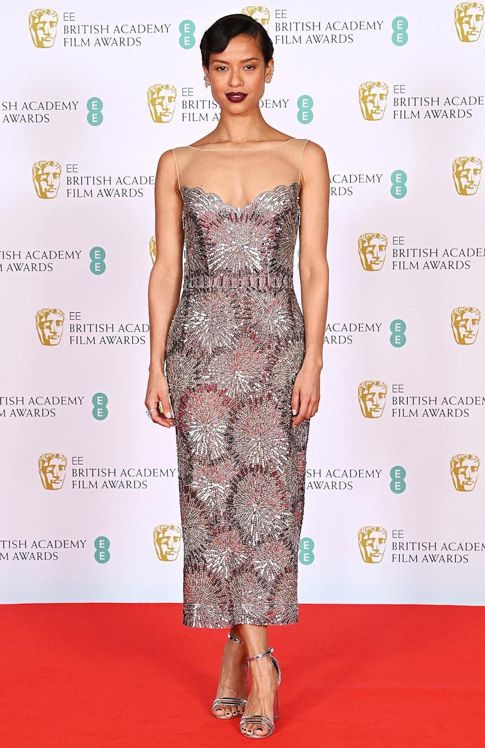 <p>in a silver embellished Louis Vuitton tea-length gown.</p>