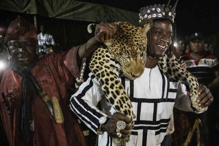 """Members of the Association of Dozos of Dafra carry the body of a leopard during a celebration of their culture in Bobo-Dioulasso, Burkina Faso, 360 kilometers (220 miles) west of the capital, Ouagadougou, on Sunday, March 28, 2021. """"Before someone faces a challenge, they know there are supernatural powers and spirits they can call upon in any situation,"""" said Jean Celestin Ky, professor of history at Joseph Ki-Zerbo University in Ouagadougou. (AP Photo/Sophie Garcia)"""