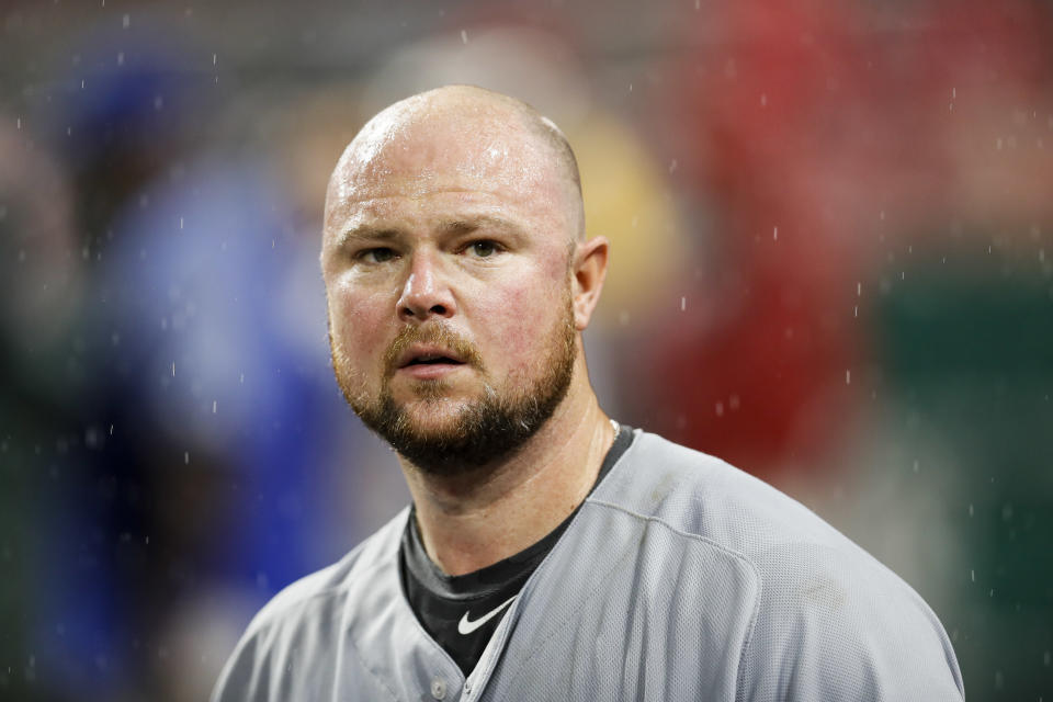 Jon Lester stands in the dugout.