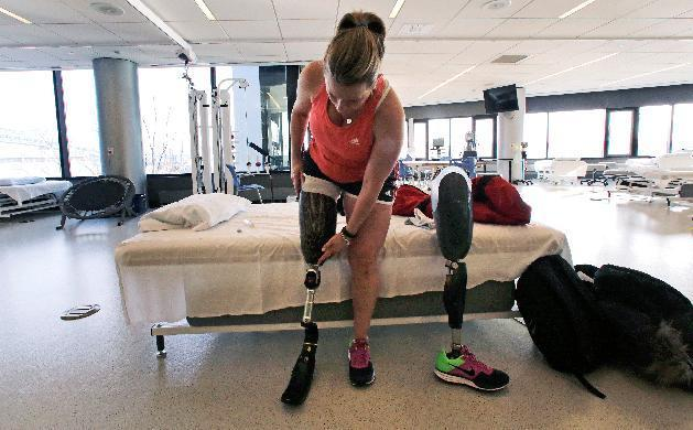 In this Tuesday, March 11, 2014 photo, Boston Marathon bombing survivor Roseann Sdoia adjusts her running blade as she switches her prosthetic legs during a therapy session at the Spaulding Rehabilitation Hospital in Boston. Sdoia, a runner who did not take part in the last year's Boston Marathon, was with friends in a crowd of fans near the finish line when one of two bombs went off nearby. (AP Photo/Charles Krupa)