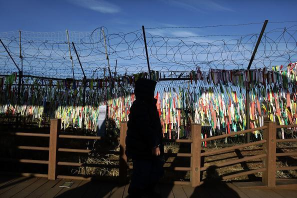 A visitor walks past prayer ribbons hanging on a barbed-wire fence at the Imjingak pavilion near the demilitarized zone (DMZ) in Paju, South Korea. North Korean media has reported that an inter-Korean communication line was reopened at the border village of Panmunjom in response to South Korea's unification minister Cho Myoung-gyon proposing holding high-level talks with North Korea ahead of winter Olympics on Feb. 9. (Photo by Chung Sung-Jun/Getty Images)