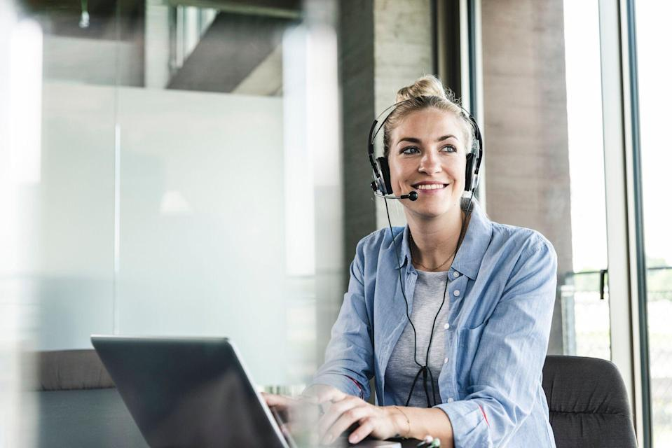 A picture of a woman with a headset and a laptop.