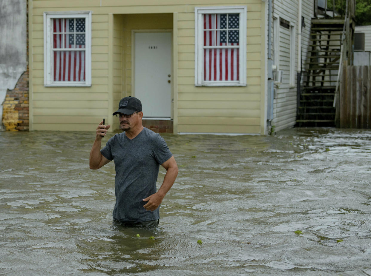 Barry Williams talks to a friend on his smartphone as he wades through storm surge from Lake Pontchartrain on Lakeshore Drive in Mandeville, La., as Hurricane Barry approaches July 13, 2019. (Photo: Matthew Hinton/AP)