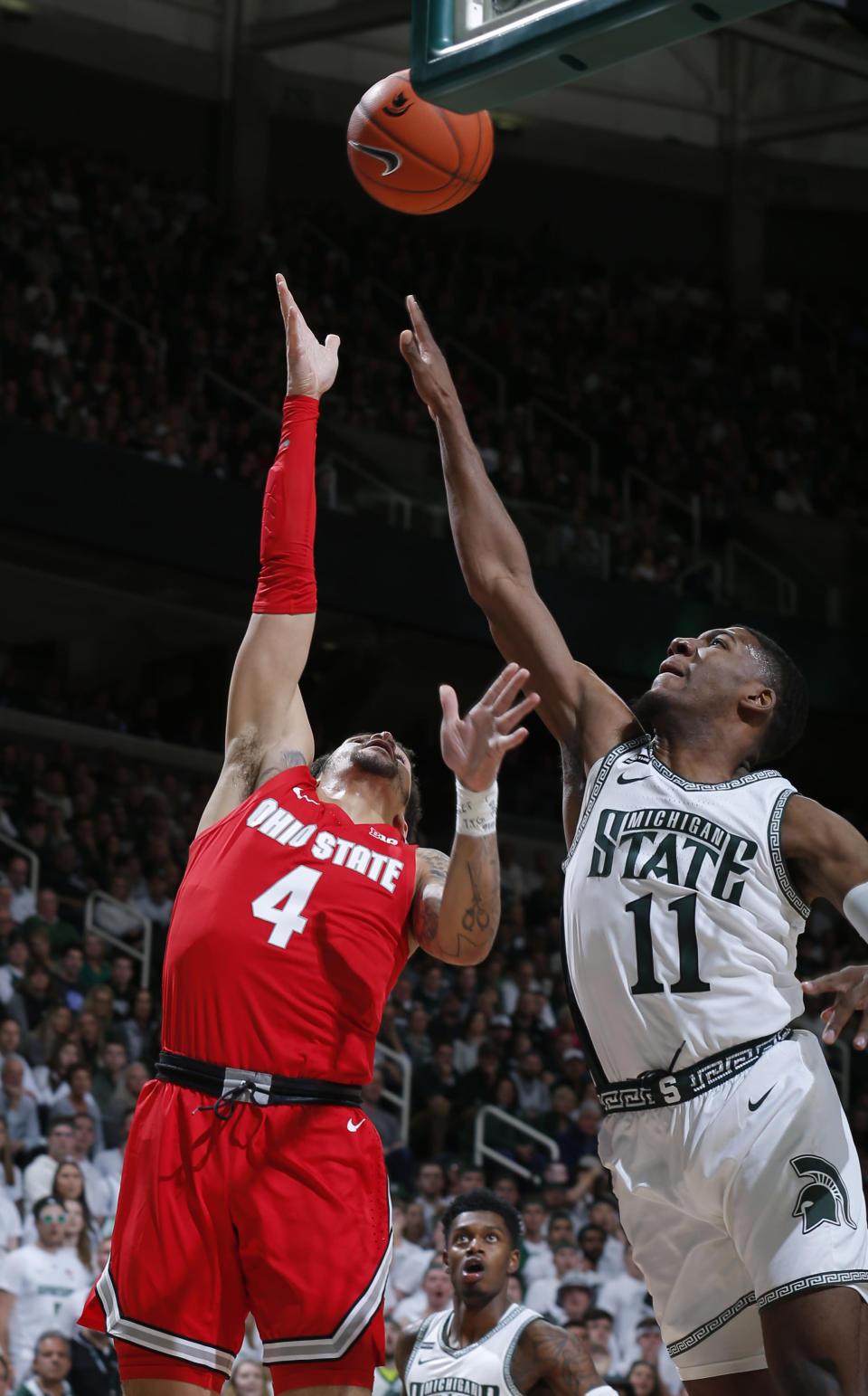 Ohio State's Duane Washington Jr., left, shoots against Michigan State's Aaron Henry (11) during the first half of an NCAA college basketball game, Sunday, March 8, 2020, in East Lansing, Mich. (AP Photo/Al Goldis)