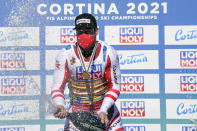 Austria's Vincent Kriechmayr sprays sparkling wine on the podium as he celebrates after winning the men's downhill, at the alpine ski World Championships in Cortina d'Ampezzo, Italy, Sunday, Feb.14, 2021. (AP Photo/Giovanni Auletta)