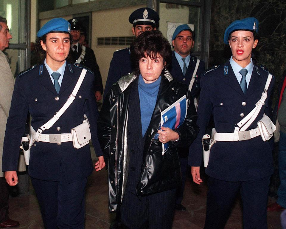 Maurizio Gucci's ex-wife Patrizia Reggiani is escorted by police officers into Milan's court in this November 3, 1998 photo. (AP Photo/Luca Bruno)