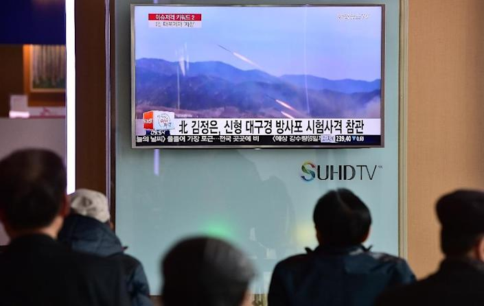 People watch a news report showing file footage of multiple North Korean rocket launchers, at a railway station in Seoul on March 4, 2016 (AFP Photo/Jung-Yeon-Je)