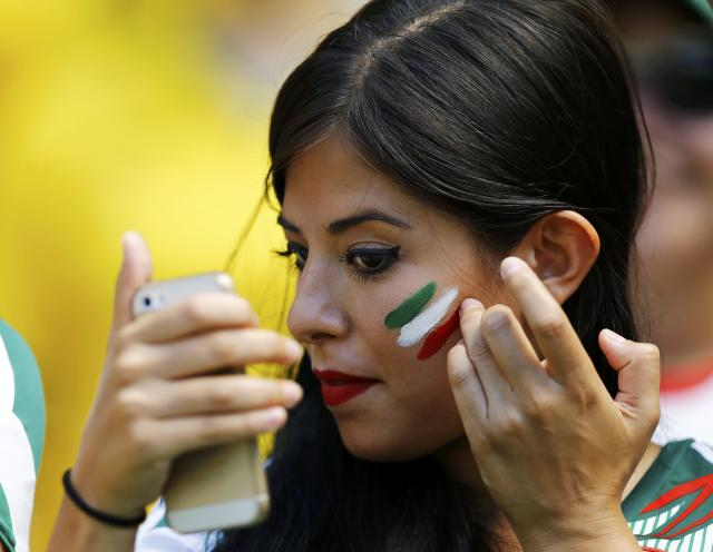 A fan of Mexico checks her phone as she applies the country's national colours onto her face before their 2014 World Cup round of 16 game against the Netherlands at the Castelao arena in Fortaleza June 29, 2014. REUTERS/Marcelo Del Pozo (BRAZIL - Tags: SOCCER SPORT WORLD CUP)