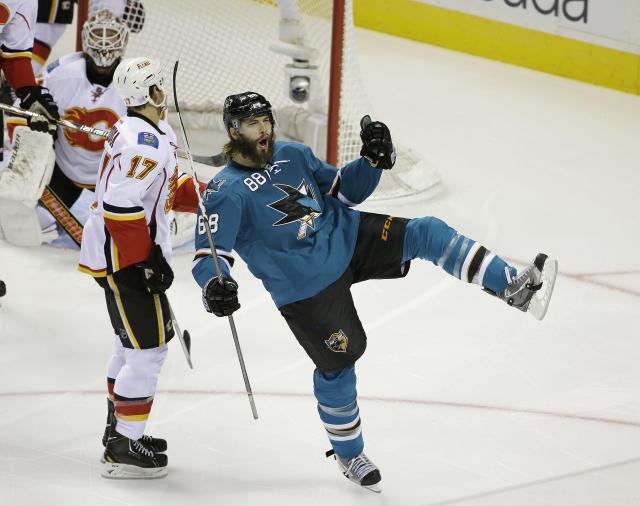 San Jose Sharks right wing Brent Burns reacts after scoring the Sharks' first goal as Calgary Flames goalie Karri Ramo, left, and Calgary Flames center Lance Bouma (17) look on during the first period of an NHL hockey game Saturday, Oct. 19, 2013, in San Jose, Calif. (AP Photo/Eric Risberg)