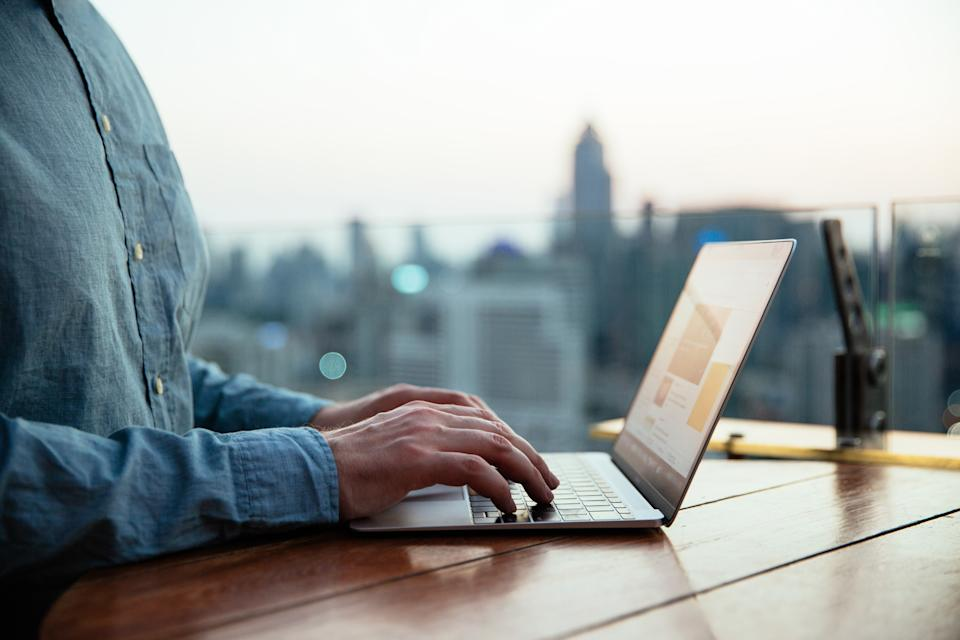 Man typing on laptop keyboard with city background