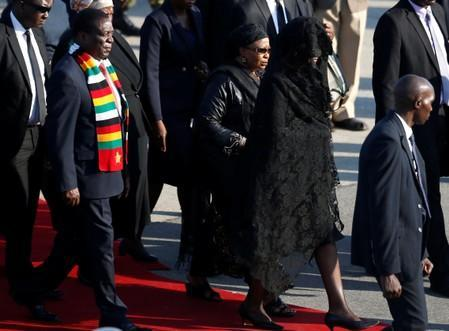 Zimbabwean President Emmerson Mnangagwa leaves with Grace Mugabe, after receiving the body of her husband, former Zimbabwean President Robert Mugabe in Harare