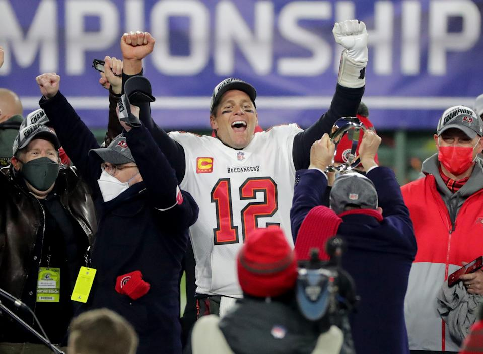 Tampa Bay Buccaneers quarterback Tom Brady celebrates during the presentation of the George Halas Trophy after the 31-26 win over the Green Bay Packers in the NFC championship game Jan. 24, 2021, at Lambeau Field.