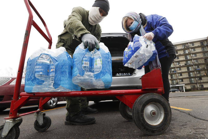 Rabbi Yosef Chesed, left, helps unload bottled water being donated from Lorie Lutz, right, at the Brightmoor Connection Food Pantry in Detroit, Monday, March 23, 2020.  The global coronavirus pandemic has brought water shutoffs in Detroit and in communities across the nation into sharp focus again amid a crucial time when officials are urging Americans to practice social distancing and basic hand-washing techniques to stop the spread of COVID-19. (AP Photo/Paul Sancya)