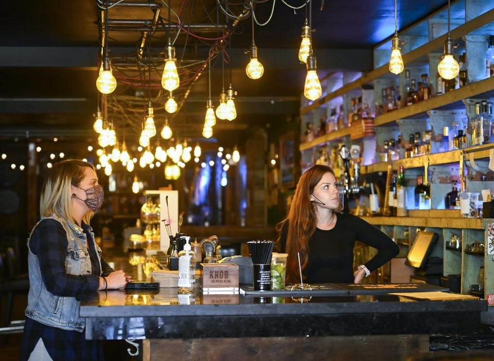 A woman wearing a mask sits at a bar while a bartender stands behind it. Both look at a TV set.