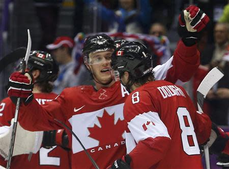 Canada's Drew Doughty (8) celebrates his game-winning overtime goal against Finland with teammate Jonathan Toews during their men's preliminary round ice hockey game at the 2014 Sochi Winter Olympics, February 16, 2014. REUTERS/Jim Young