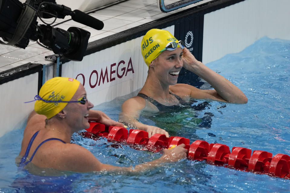 Emma Mckeon, right, of Australia, and Sarah Sjoestroem, of Sweden, smile as they look at the results after competing in the women's 50-meter freestyle final at the 2020 Summer Olympics, Sunday, Aug. 1, 2021, in Tokyo, Japan. Mckeon won gold and Sjoestroem took silver. (AP Photo/Jae C. Hong)