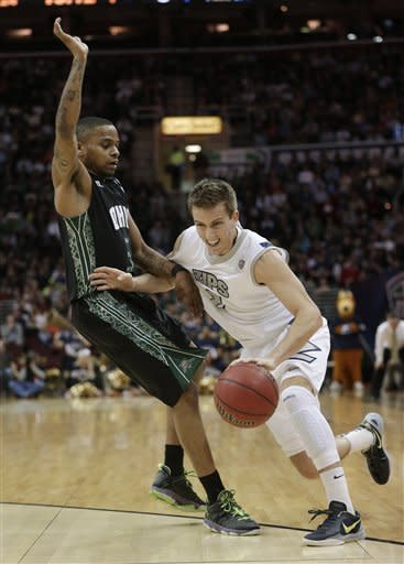 Akron's Brian Walsh, right, drives past Ohio's D.J. Cooper during the first half of an NCAA college championship basketball game in the Mid-American Conference tournament on Saturday, March 16, 2013, in Cleveland. (AP Photo/Tony Dejak)