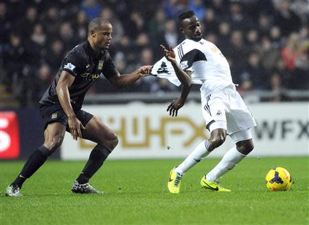 Swansea City's Roland Lamah is fouled by Manchester City's Vincent Company (L) during their English Premier League soccer match at the Liberty Stadium in Swansea, Wales, January 1, 2014. REUTERS/Rebecca Naden