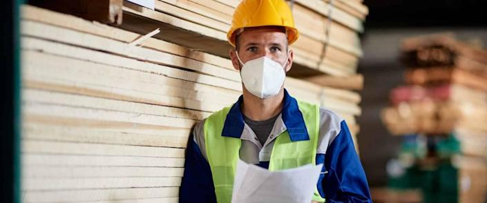 Portrait of warehouse worker in timber storage compartment wearing face mask due to coronavirus pandemic.