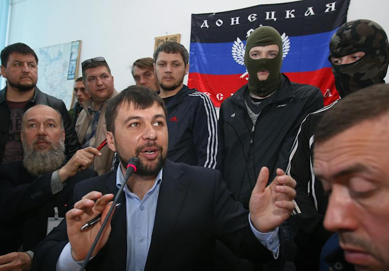Denis Pushilin, foreground center, spokesman of the self-appointed Donetsk People's Republic, speaks to reporters inside the regional administration building seized earlier in Donetsk, Ukraine, Friday, April 18, 2014. Pushilin told reporters that the insurgents do not recognize the Ukrainian government as legitimate. Pro-Russian insurgents in Ukraine's east who have been occupying government buildings in more than 10 cities said Friday they will only leave them if the interim government in Kiev resigns.(AP Photo/Sergei Grits)
