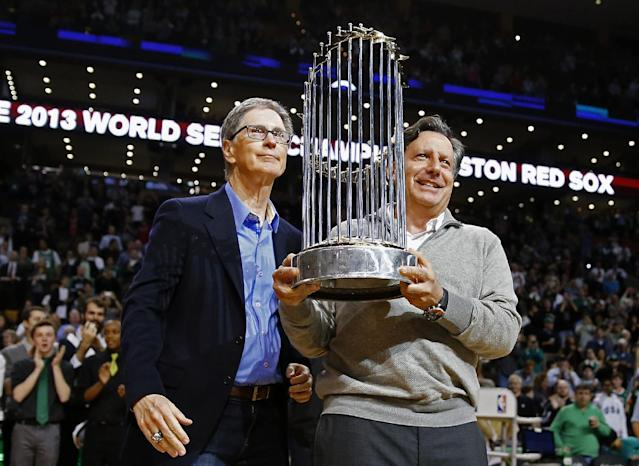 Boston Red Sox owner John Henry, left, and chairman Tom Werner hold the World Series trophy before an NBA basketball game between the Boston Celtics and the Milwaukee Bucks in Boston, Friday, Nov. 1, 2013. (AP Photo/Michael Dwyer)