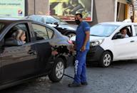 A worker wearing a protective face mask fills up a car with fuel, at a gas station in Beirut