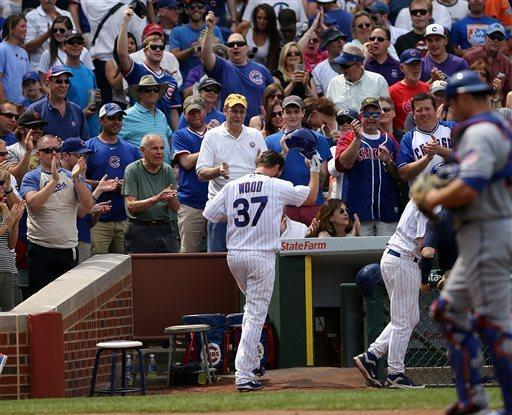 Chicago Cubs' Travis Wood tips his hat to the crowd after his two run home run in the fifth inning against the New York Mets in the MLB National League baseball game in Chicago on Sunday, May 19, 2013. (AP Photo/Charles Cherney)