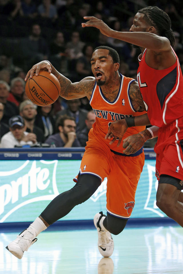 New York Knicks' J.R. Smith (8) drives against Atlanta Hawks' DeMarre Carroll, right, during the first half of an NBA basketball game Saturday, Nov. 16, 2013, in New York. (AP Photo/Jason DeCrow)