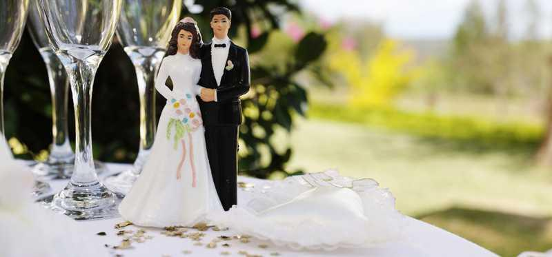 Bride and groom cake toppers sit on a table.